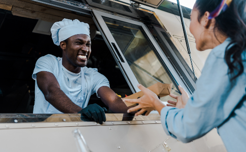 man in truck giving food to woman